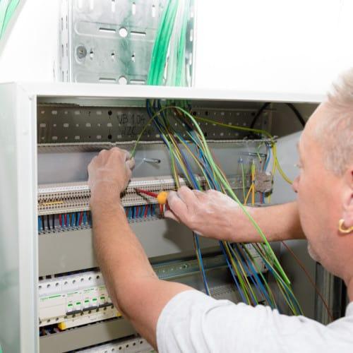 Elektriciteitswerken Gielen NV elektricien werkt aan zekeringskast bij bekelaar